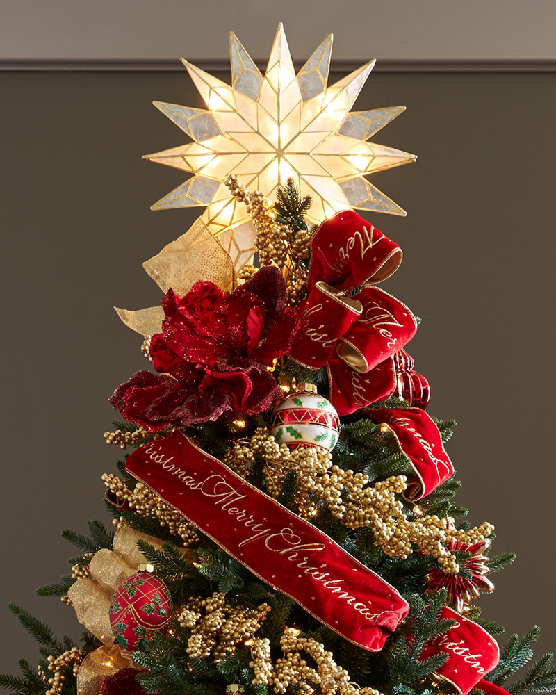 A red ribbon and lighted star tree topper placed on top of a Christmas tree