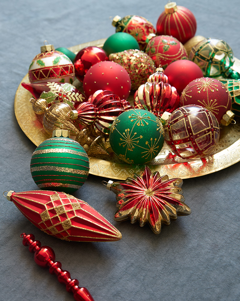 Closeup shot of assorted red, green, and gold Christmas ornaments placed on a gold plate