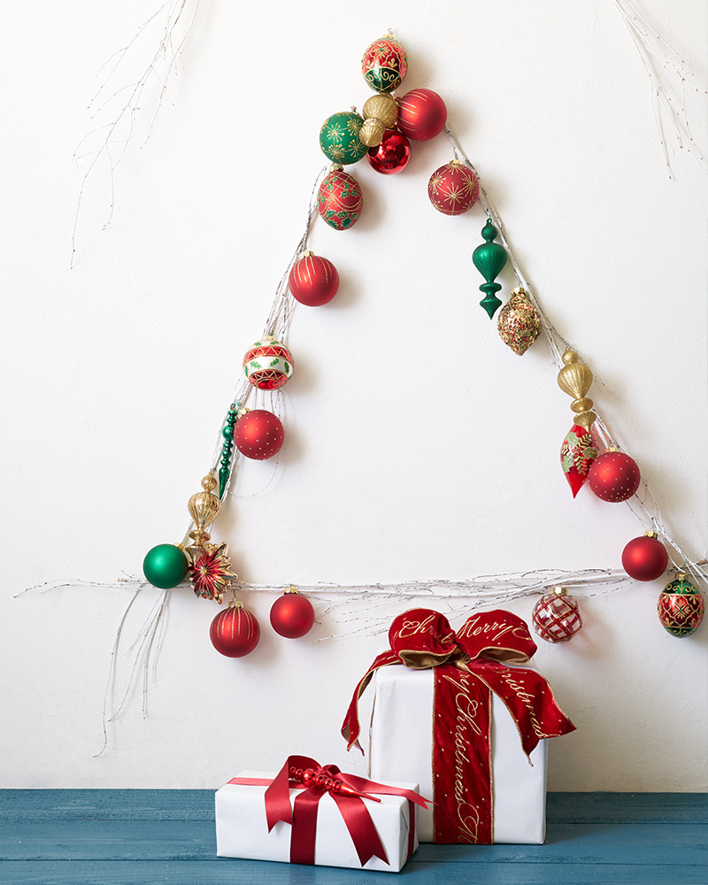 A white wall decorated with white twigs and red, green, and gold ornaments