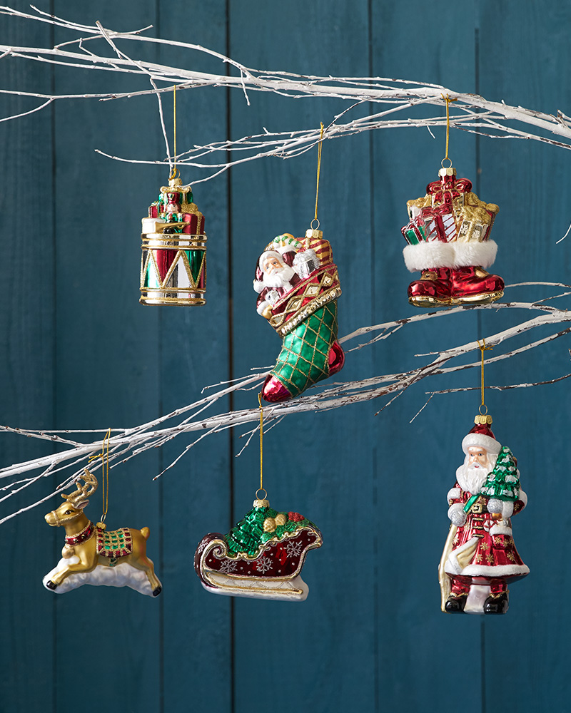 Closeup shot of assorted holiday figures hanging from white twigs