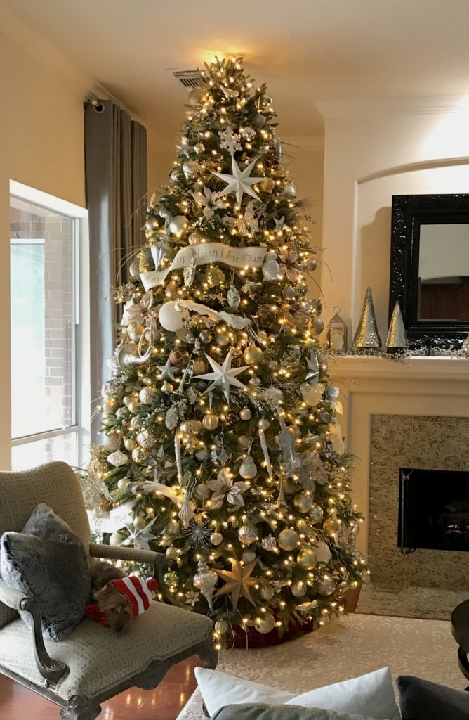 Full shot of artificial Christmas tree with silver and gold ornaments and decorations