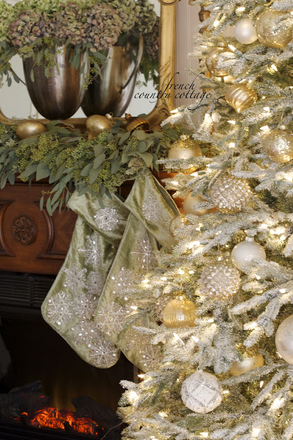 Closeup shot of a lit-up Christmas tree with frosted branches, assorted white and gold ornaments, and presents underneath