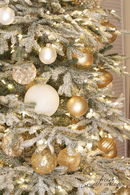 Closeup shot of a lit-up Christmas tree with frosted branches and assorted white and gold ornaments