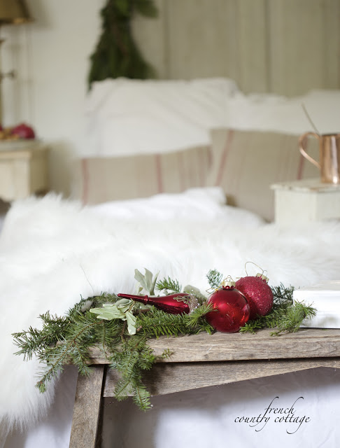 A bunch of pine branches with red ornaments on the foot of a bed