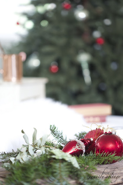 A bunch of pine branches decorated with red ornaments with an Elegant Simple Vintage Christmas Tree as background