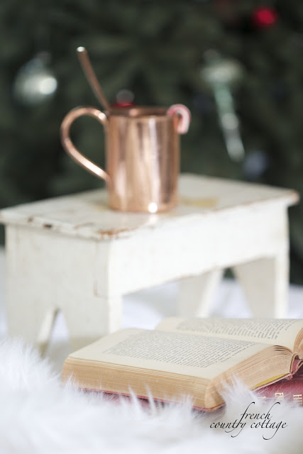 Book beside an aged wooden stool with copper mug