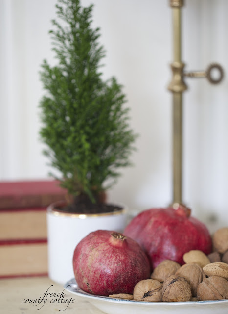 Fruits and nuts on a dish beside a small potted Christmas tree