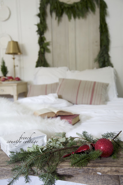 A bunch of pine branches with red ornaments at the foot of the bed with garland on headboard