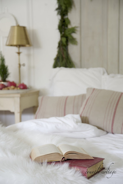 Books on bed with white fluffy sheets and white, red, and beige pillows