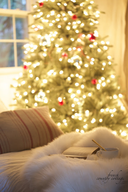 Book, cup, fur blanket, and pillow beside a lighted Elegant Simple Vintage Christmas tree
