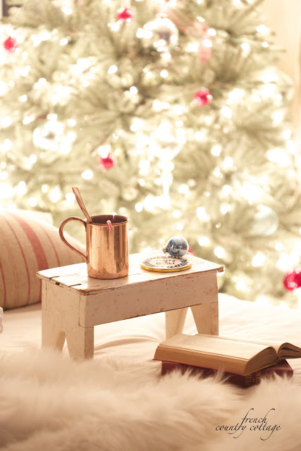 Bed with fur blanket, books, throw pillow, and vintage stool with copper mug and Christmas coaster beside a lighted elegant simple vintage Christmas tree