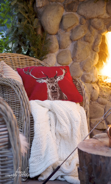 A wicker chair with a red reindeer pillow and knit blanket by the fireplace