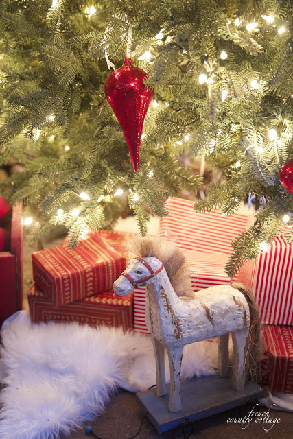Closeup shot of a toy wooden horse placed under a lit-up Christmas tree