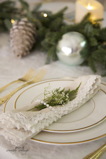 Table set up with pinecone, evergreen foliage, and ornaments