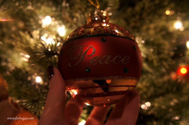"""Closeup shot of a red Christmas ornament with the word """"peace"""" imprinted in glitter"""