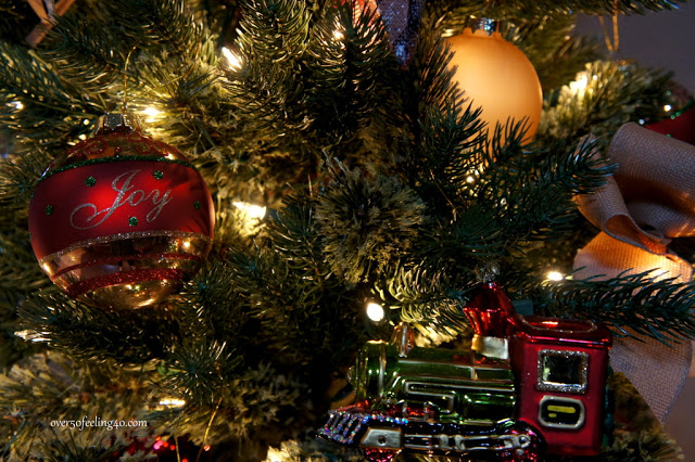 Closeup shot of a Christmas tree decorated with ornaments and a toy truck