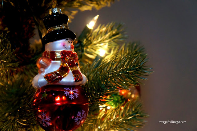 Closeup shot of a snowman ornament hanging from a Christmas tree