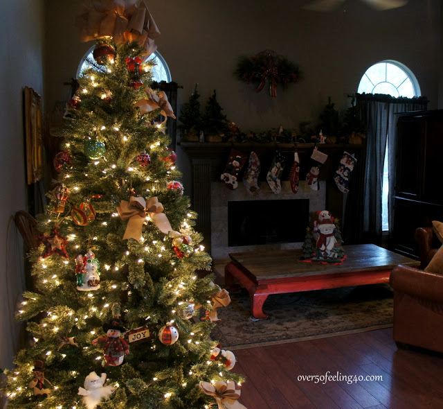 Wide shot of a room with a lit-up artificial Christmas tree adorned with various ornaments