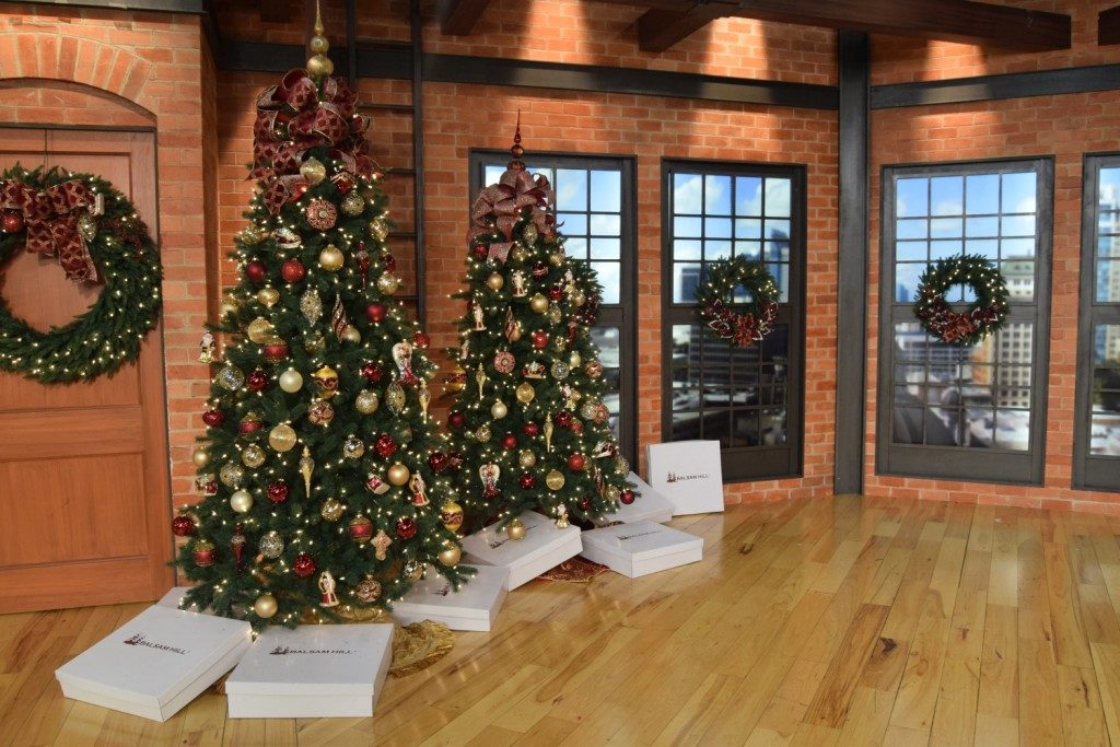 Artificial Christmas trees and foliage decorated with red and gold theme