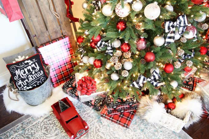 Shot of a Christmas tree decorated with red, white, and black ornaments beside a sled