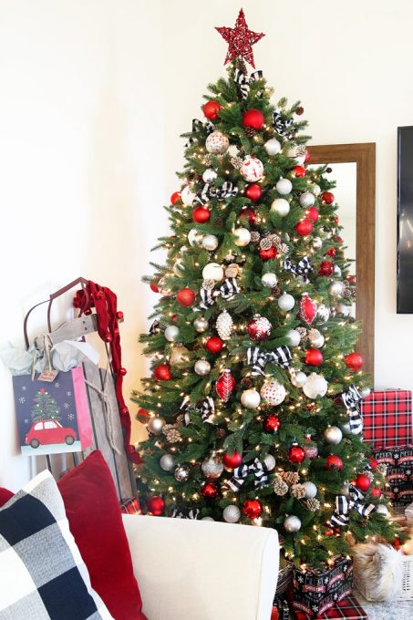 Artificial Christmas tree decorated with red, white, and black ornaments beside a mirror and a sled
