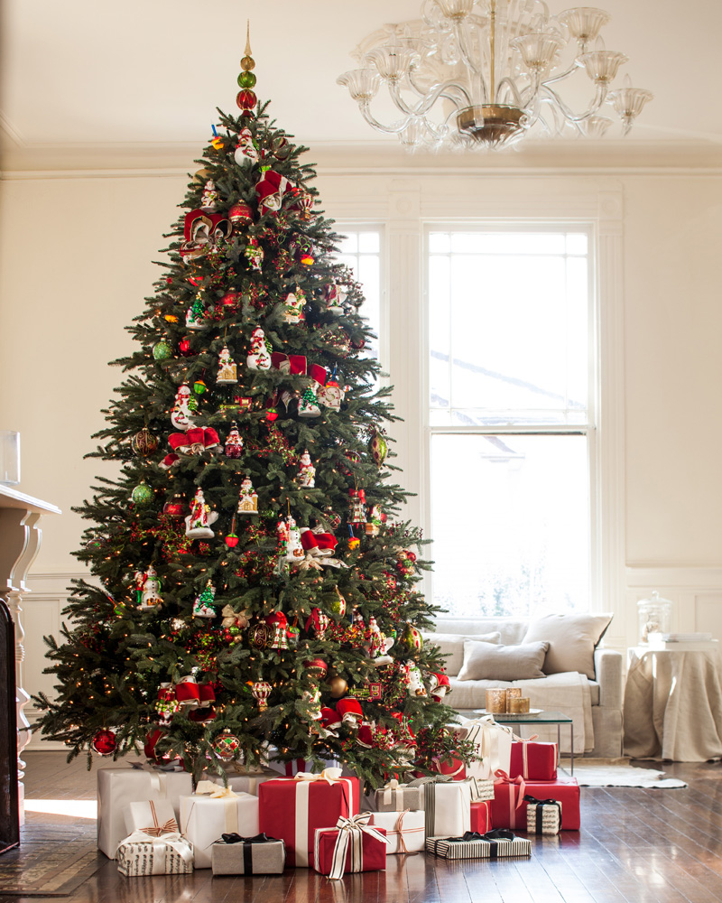A lit-up Christmas tree decorated with assorted ornaments and presents underneath