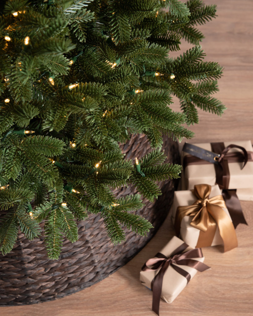 Balsam Hill New BH Fraser Fir Tree bottom on top of a Christmas tree collar on hardwood floor with Christmas gifts in kraft paper with brown and gold ribbons