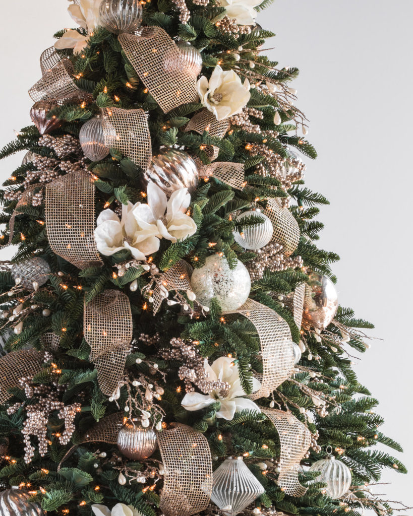 christmas tree with ornaments, ribbon, and floral picks