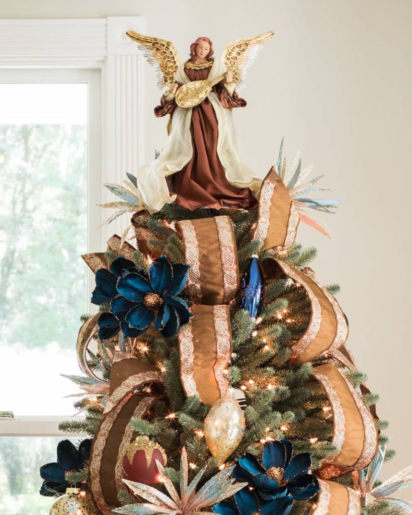 christmas tree decorated with floral picks, ribbons, and angel tree topper