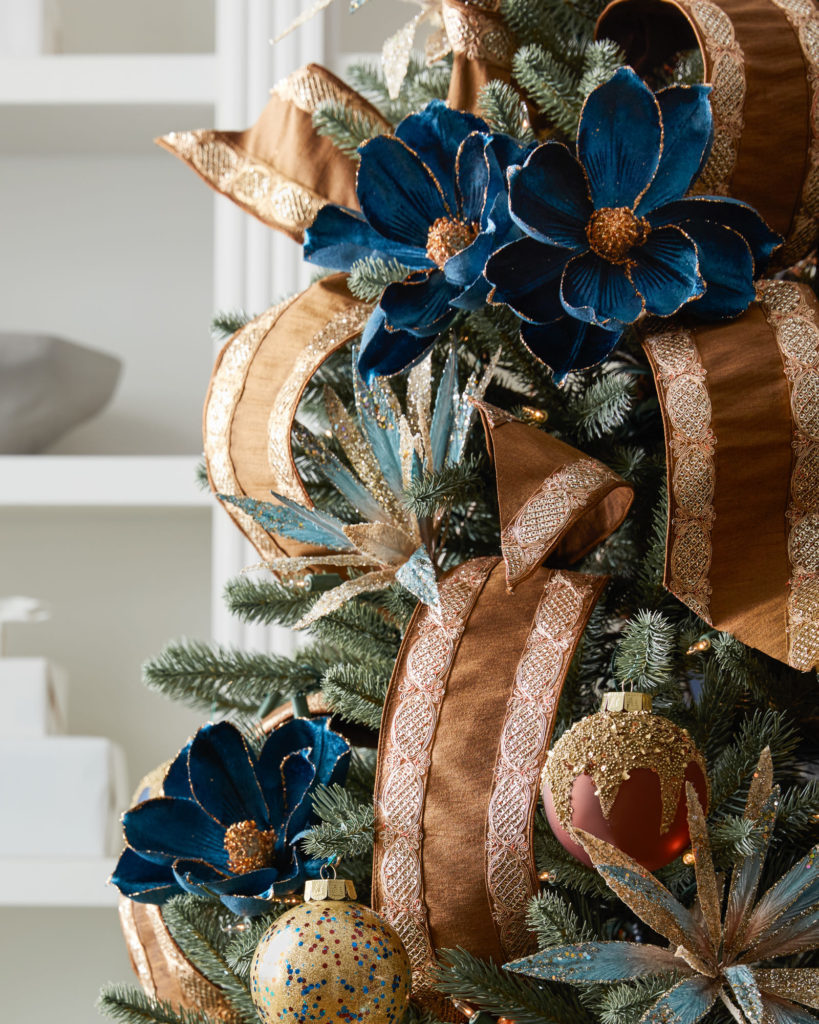 artificial christmas tree with floral picks and ribbon