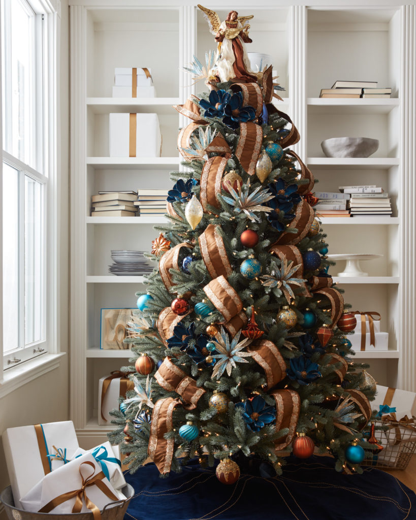 full shot of artificial Christmas tree decorated with ribbon