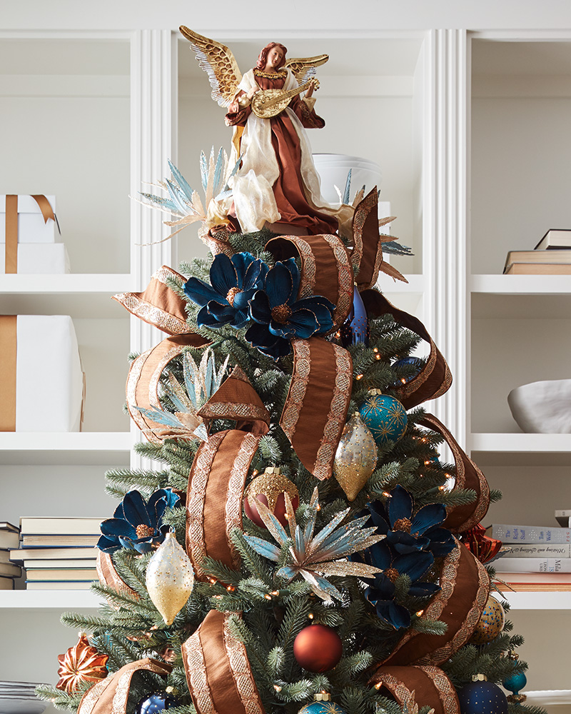 christmas tree with ribbon, floral picks, ornaments, and tree topper