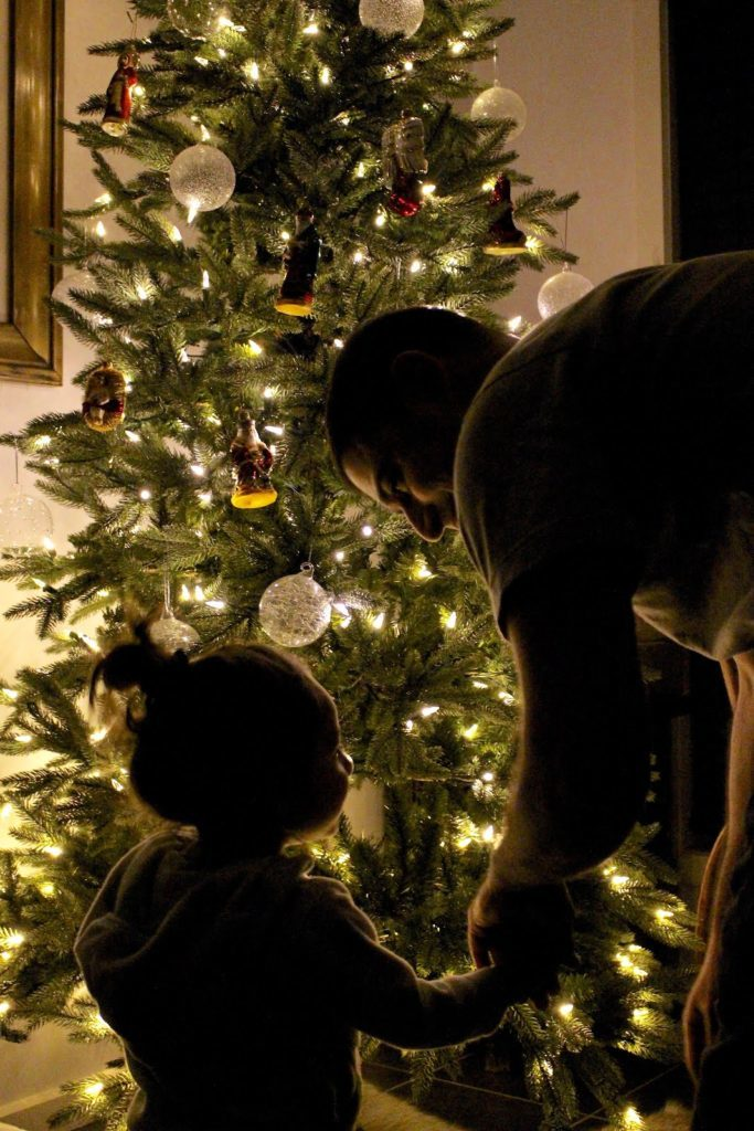 Silhouettes of a child and a man in front of a lit-up Christmas tree