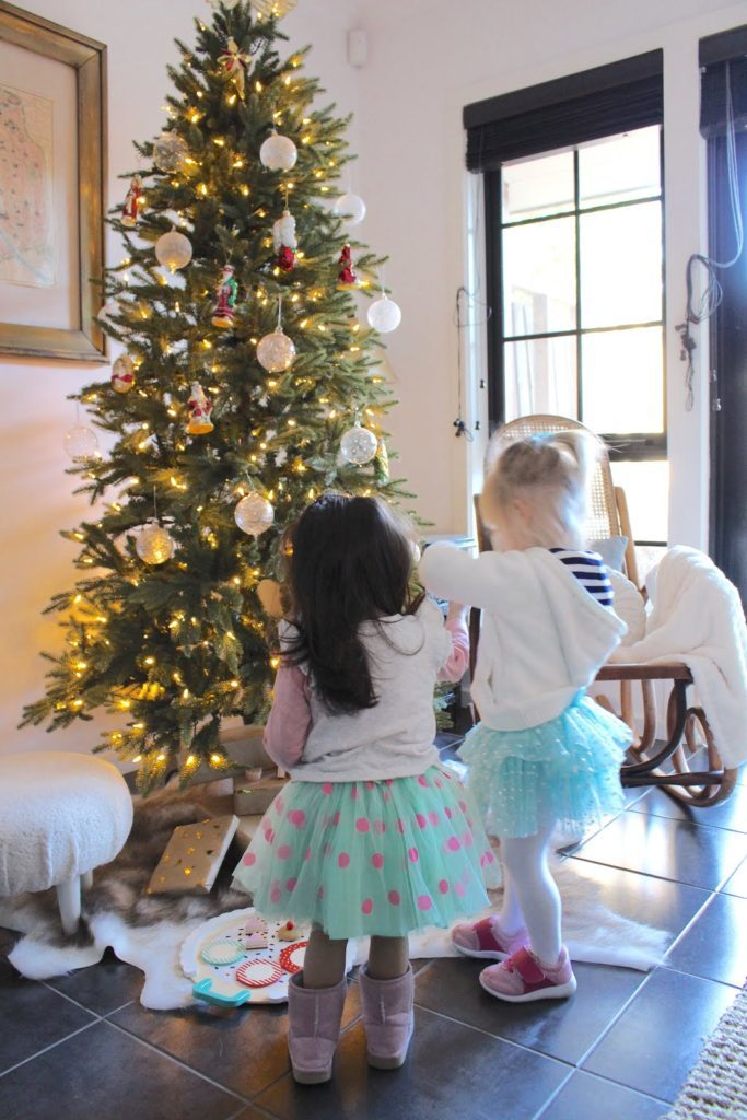 Two kids standing in front of a Christmas tree