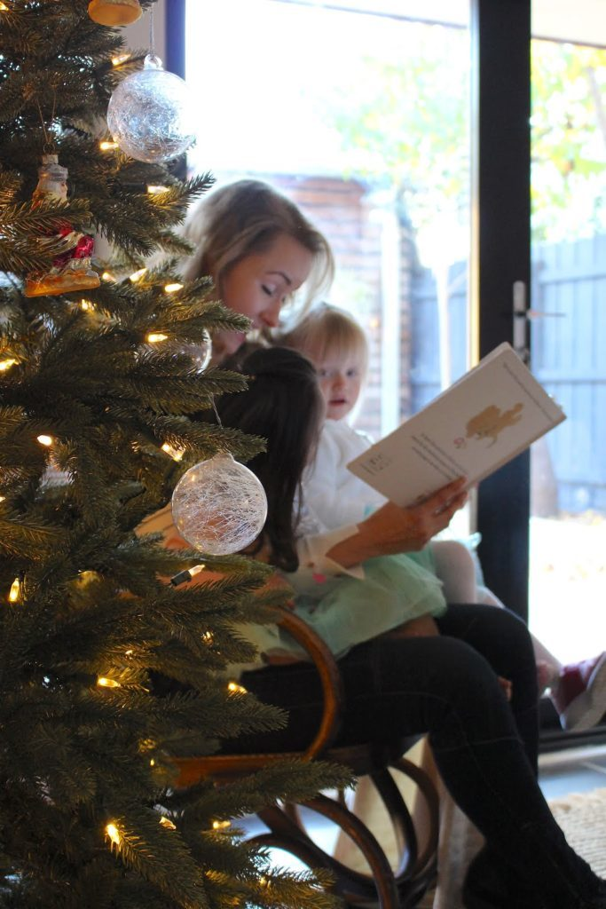 A woman and two young girls reading a book behind a Christmas tree