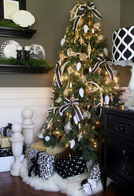 A lit-up Christmas tree placed in a corner and decorated with black and white ribbons and assorted ornaments