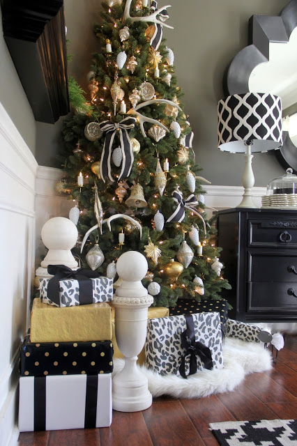 A Christmas tree in a corner decorated with ribbons and assorted ornaments.
