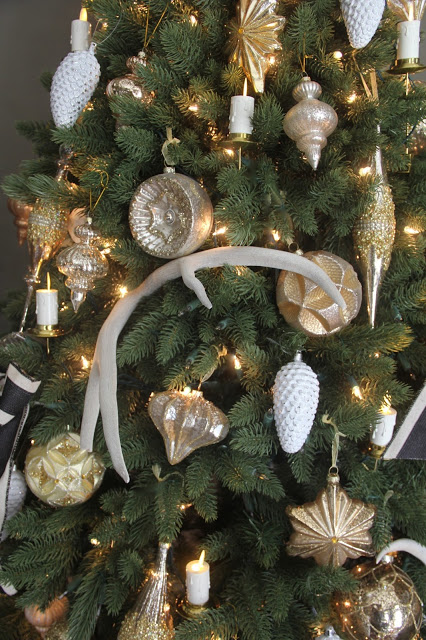 Closeup shot of a lit-up Christmas tree adorned with assorted ornaments
