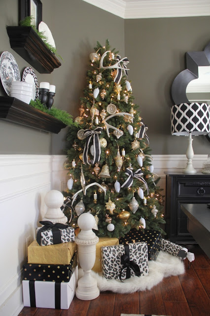 A corner of a room with a Christmas tree decorated with ribbons and assorted ornaments