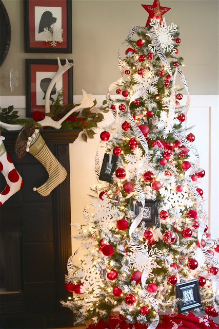 An artificial Christmas tree decorated with white snowflake ornaments and red Christmas balls.