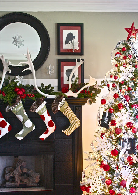 Christmas stockings hanging over a mantel beside a Christmas tree decorated with red and white ornaments.