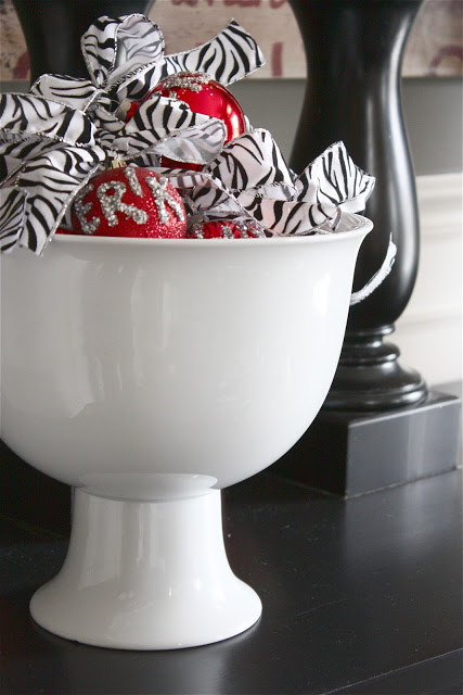 A closeup shot of a white bowl filled with zebra stripes patterned bows and red metallic Christmas ornaments