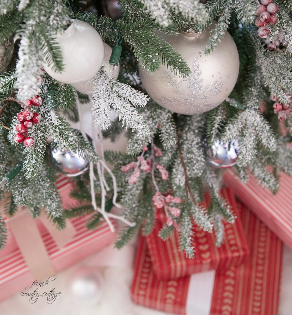 Closeup shot of a Christmas tree with frosted branches, white ornaments, red berry picks, and presents underneath