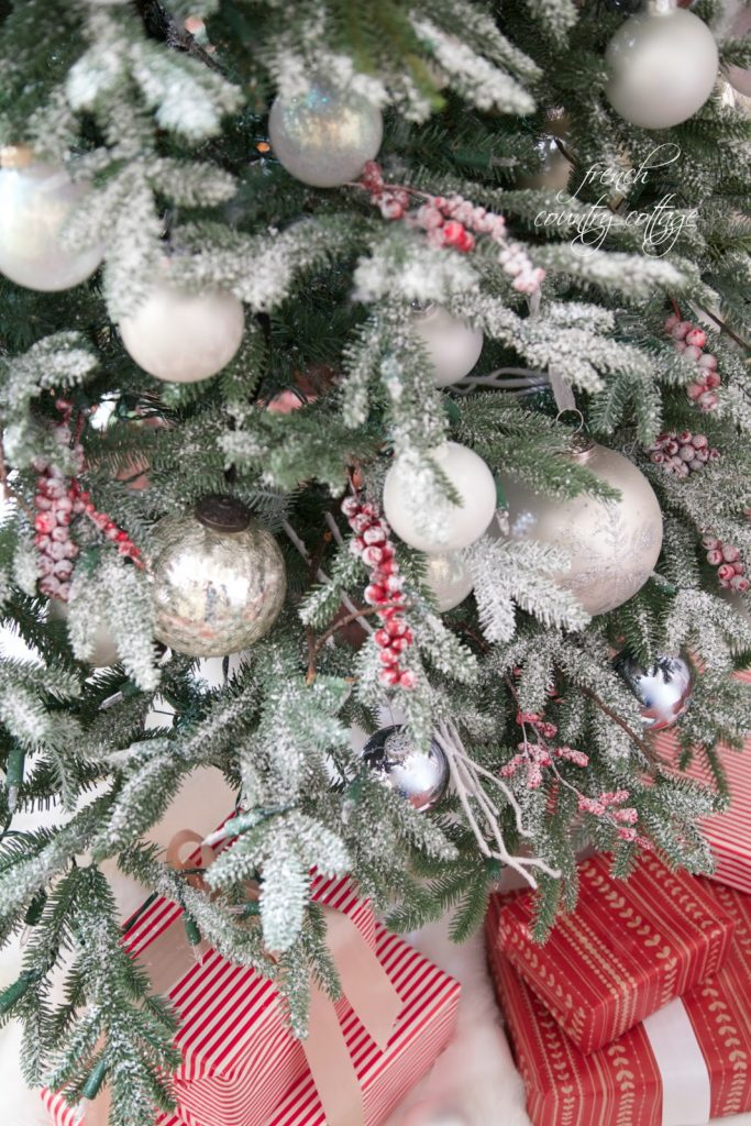 Closeup shot of a Christmas tree with frosted branches, assorted white ornaments, and frosted red berry picks.