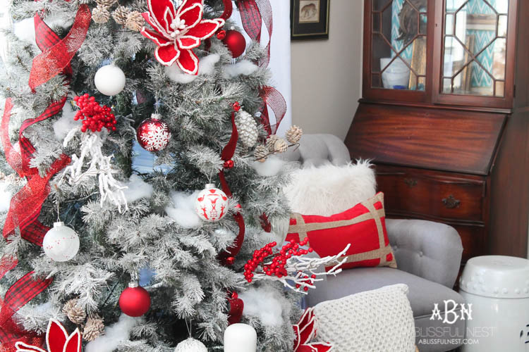 Red and white decorations on frosted artificial Christmas tree