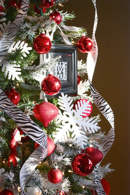 A closeup shot of a Christmas tree decorated with zebra stripes ribbons, white snowflakes, and red ornaments