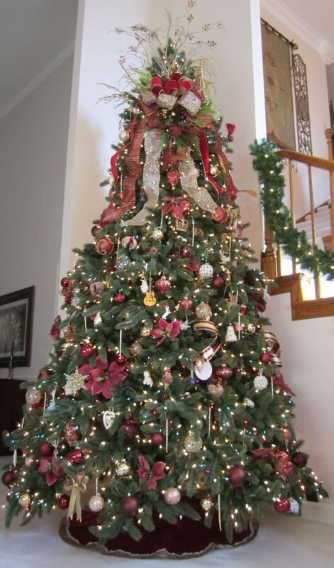 full shot of artificial Christmas tree decorate with silver and burgundy ornaments