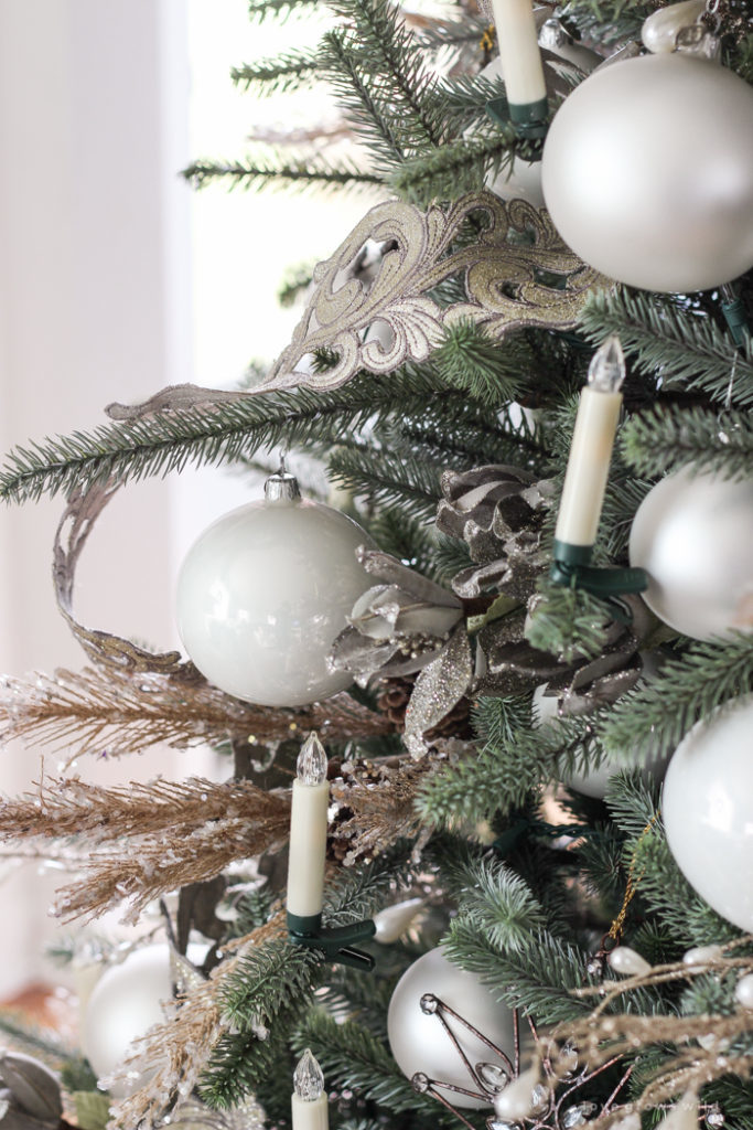 close up of white christmas balls and candles on tree