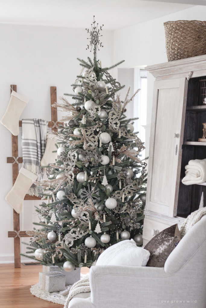 decorated christmas tree with tree topper, ribbon, balls, candles, and picks