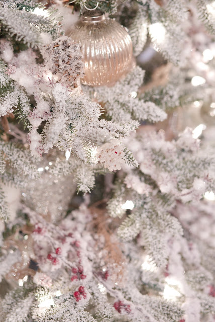 close up of french country ornaments and snowy picks on frosted tree